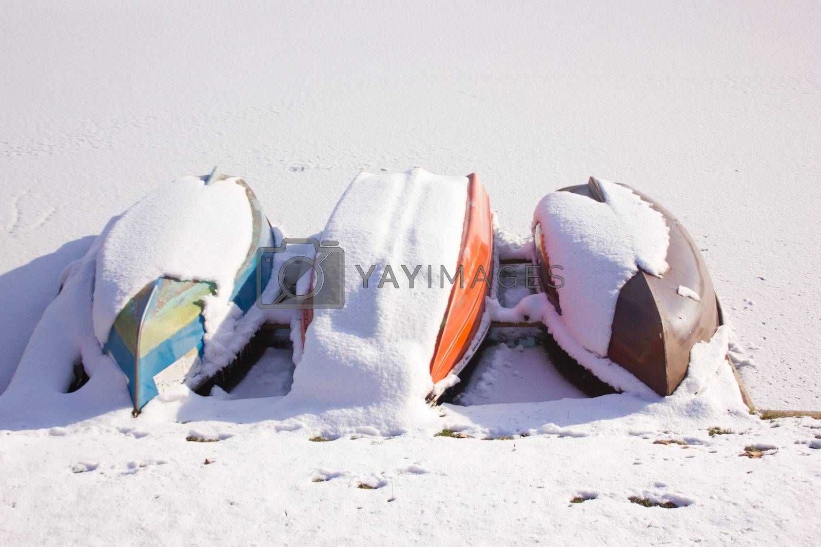 Boats on frozen lake covered with snow