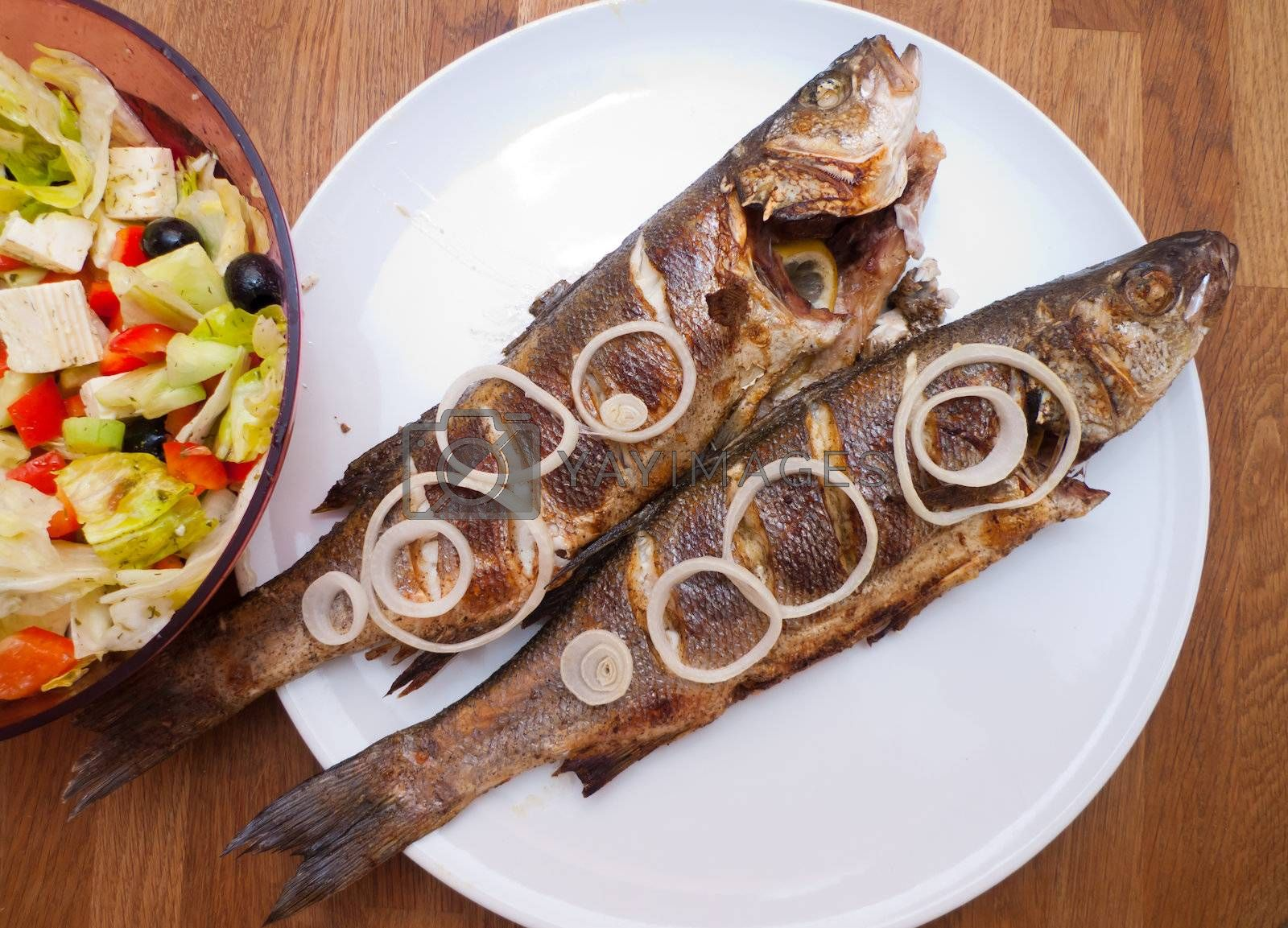Photo of two grilled fishes ready to eating