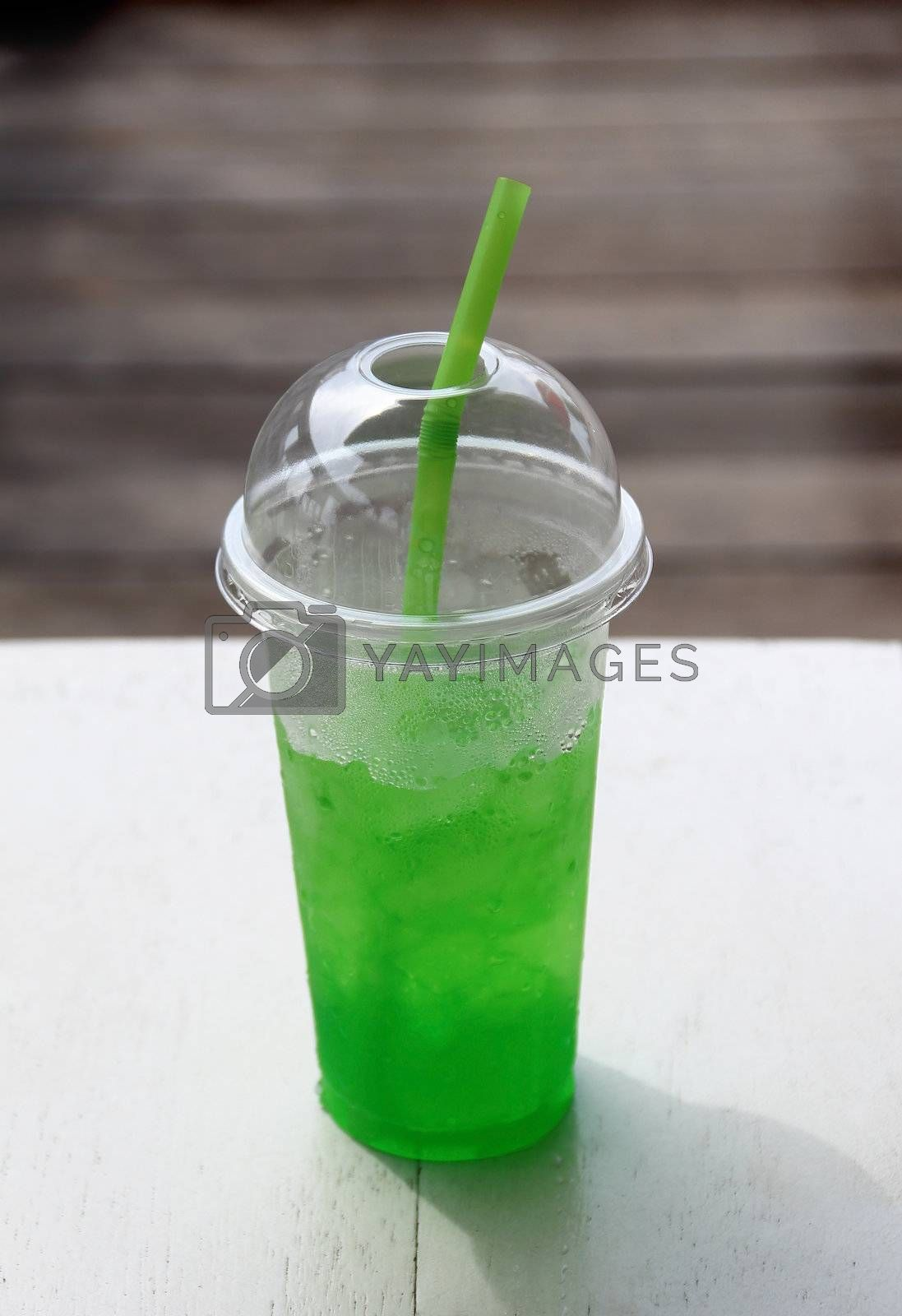 Soft drink in plastic cup with green straw