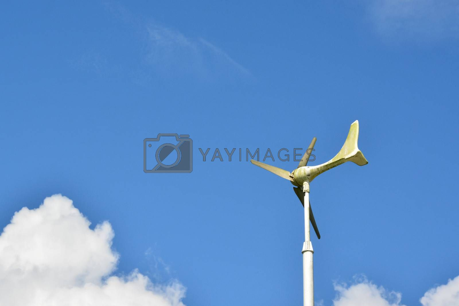 Windmill or weather vane against blue sky.