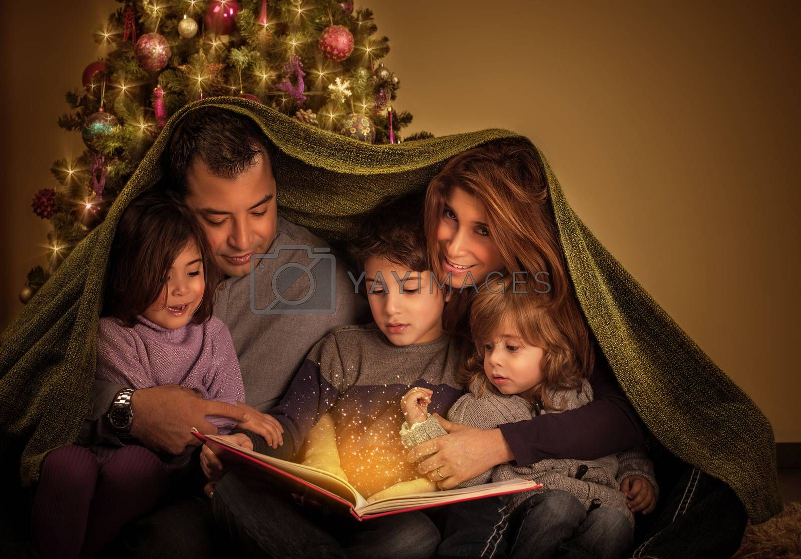 Big family reading interesting magic story in Xmas eve, happy parents with cheerful children covered with blanket, Christmas tree at home, New Year celebration
