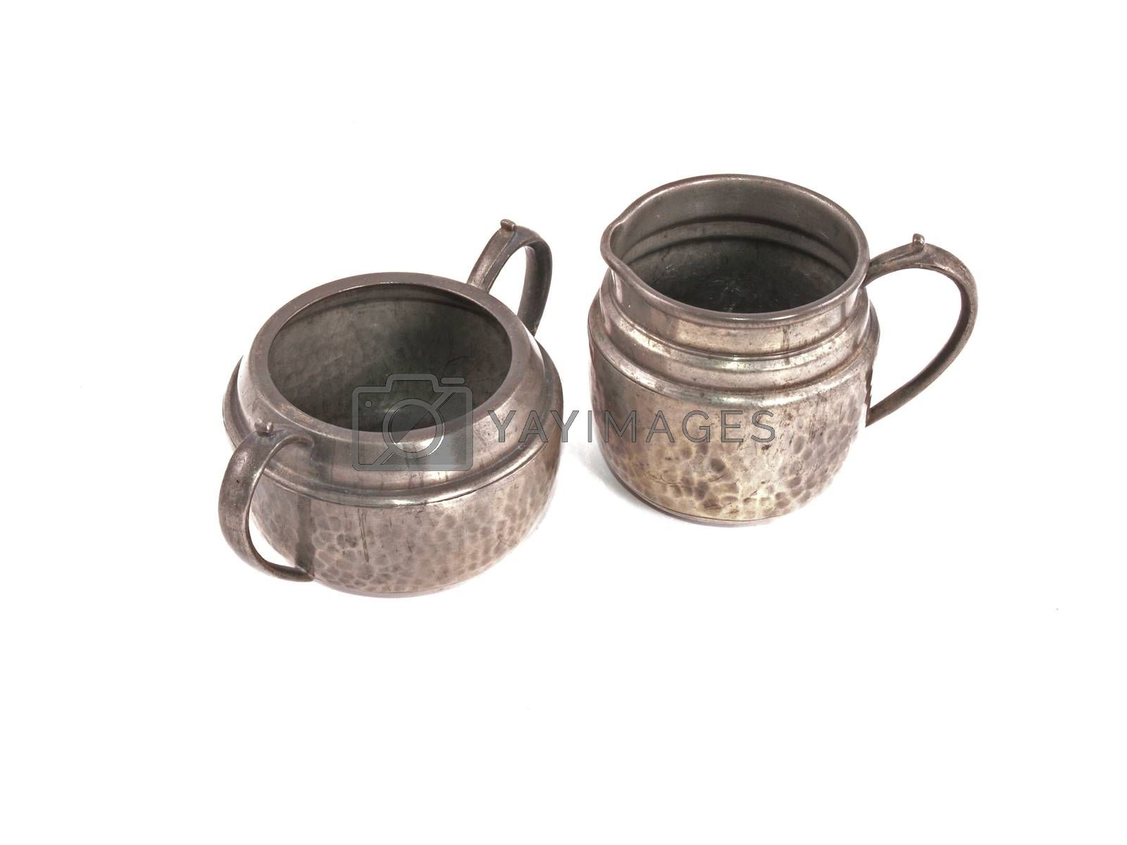 Pewter sugar bowl and milk jug on a white background.