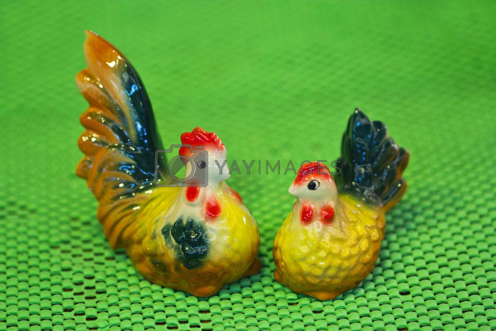Cute ceramic chicken on green background, in Thailand.