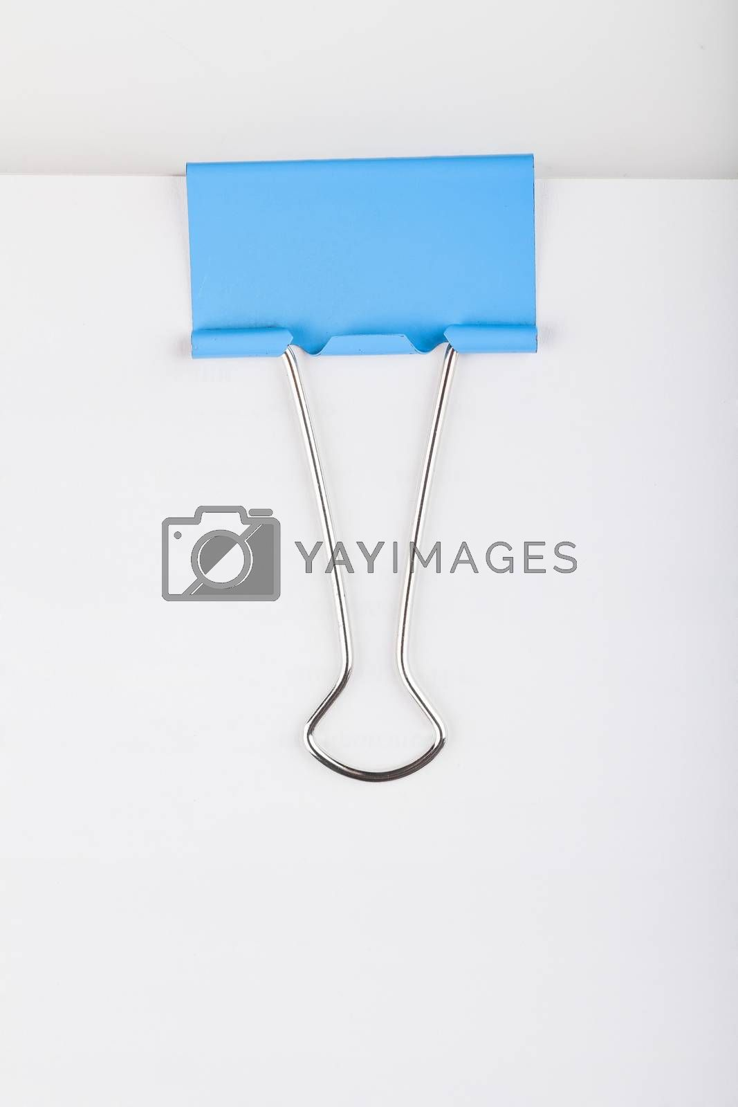 Macro view of blue paper clip on a bunch of paper sheets