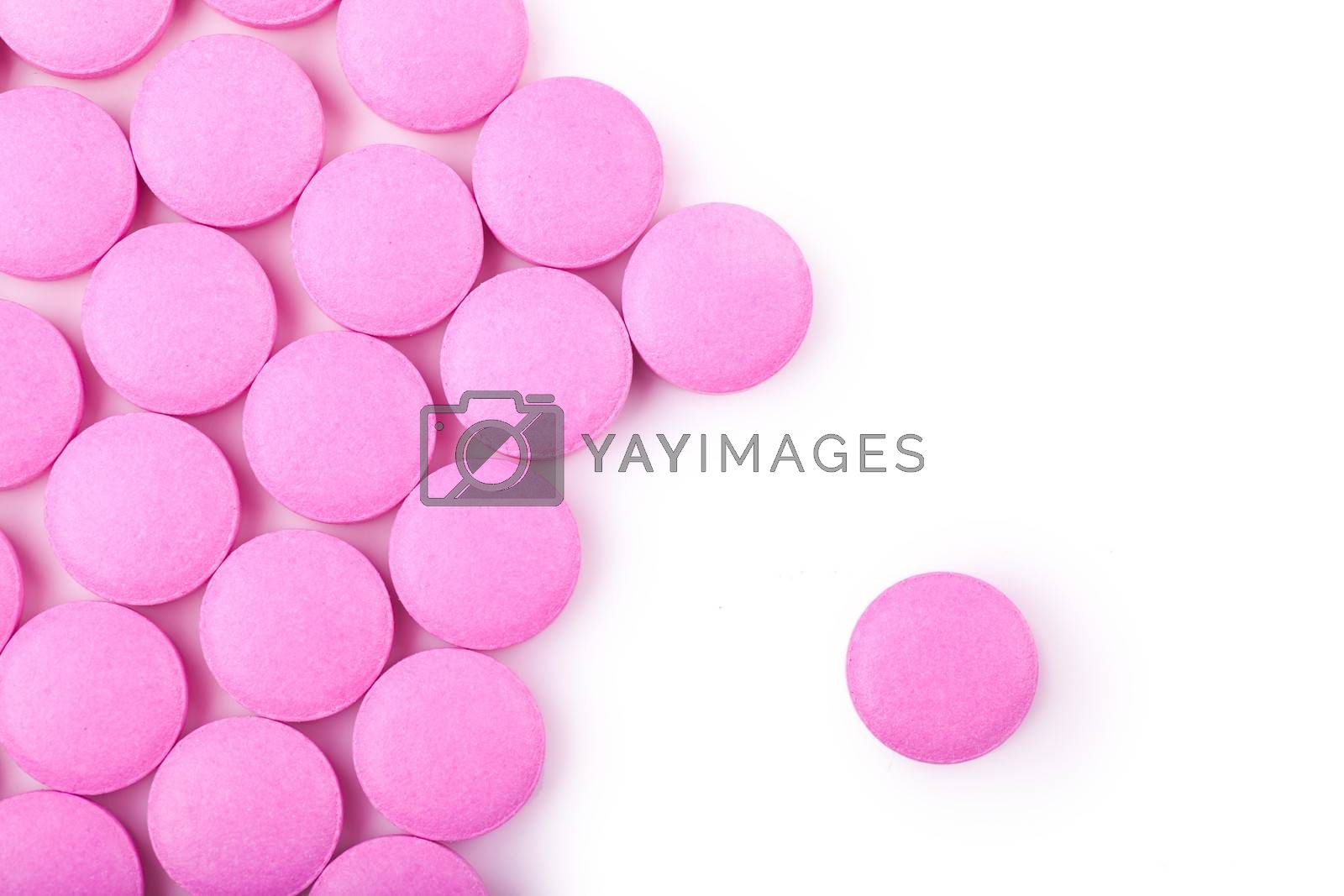 Macro view of pink pills over white background