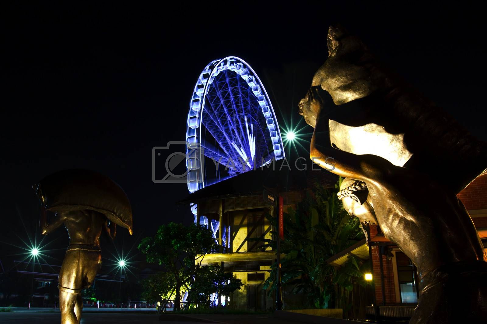 Bangkok at twilight in the dark of sky with ferris wheel background and foreground of the chinese labor statue