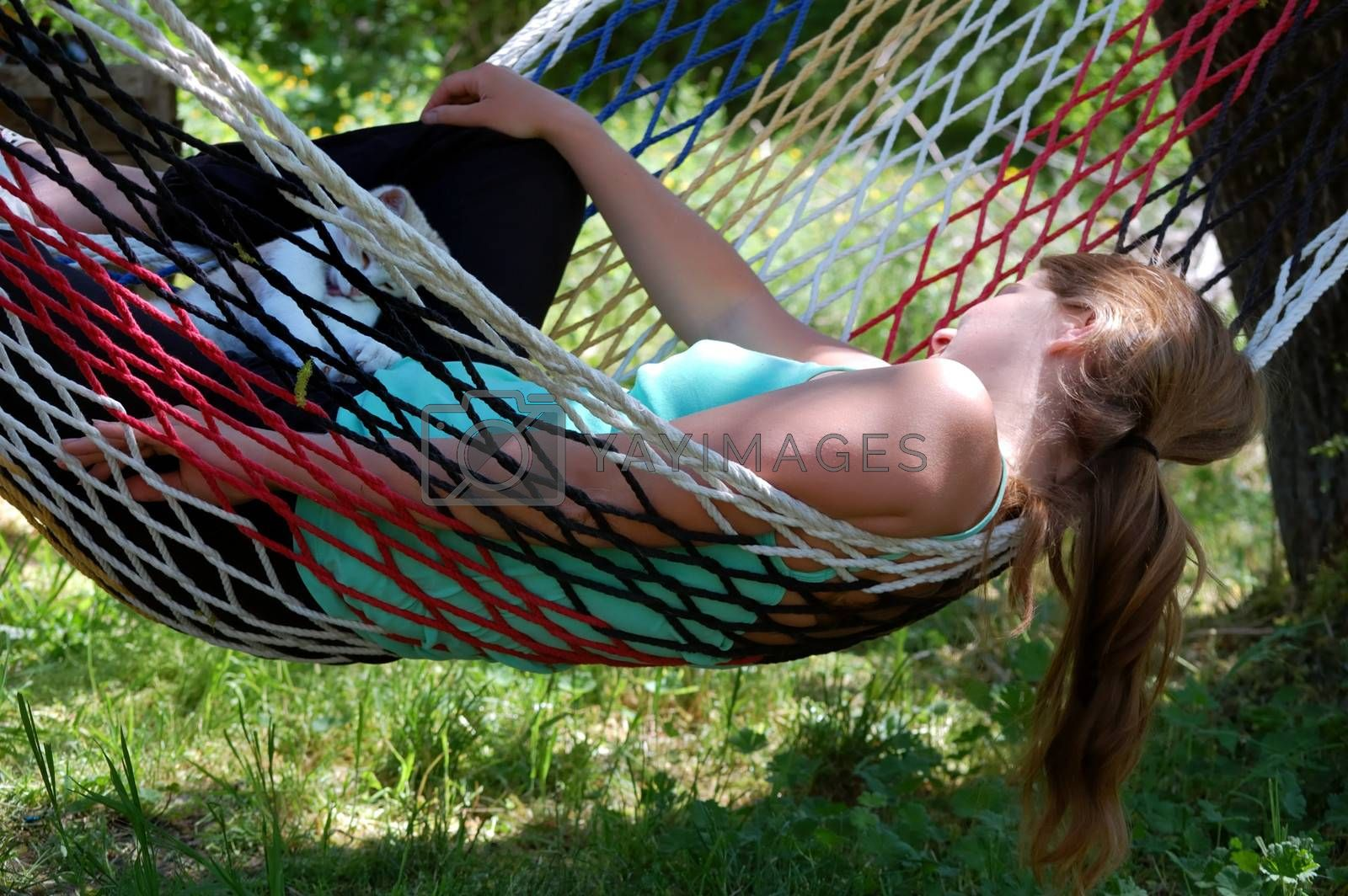 girl resting in a hammock and plays with a white kitten
