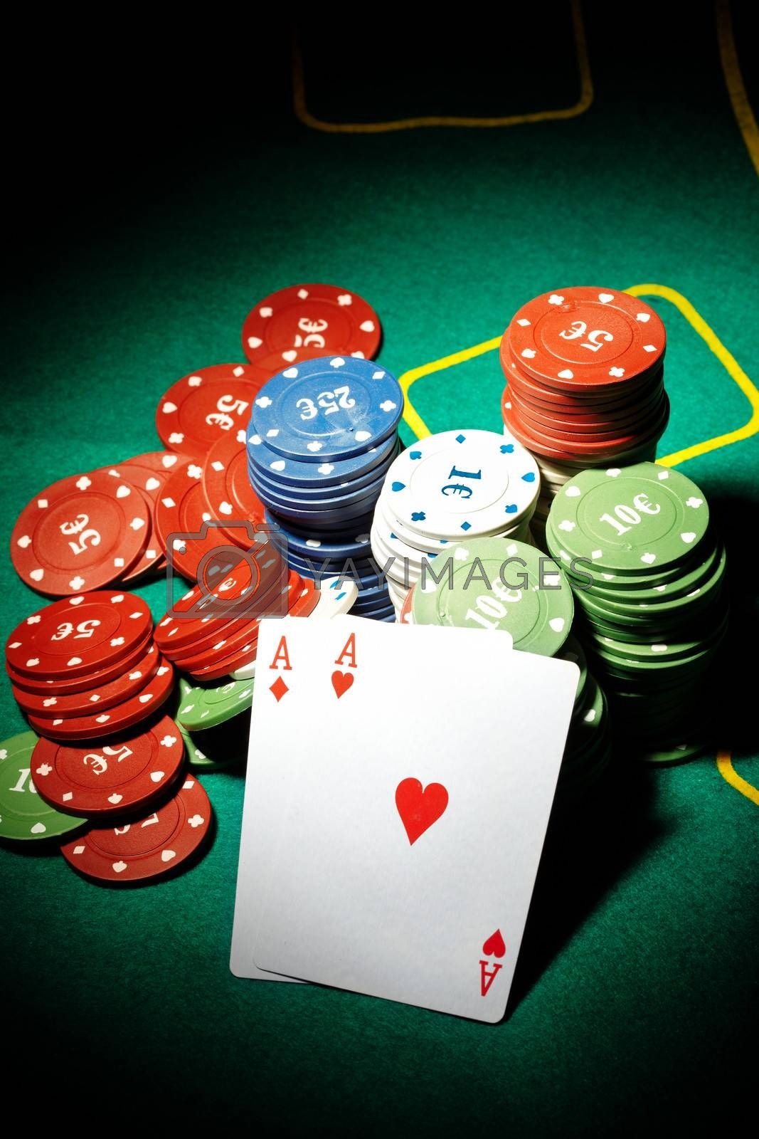 Pair of aces and poker chips on a green table in casino