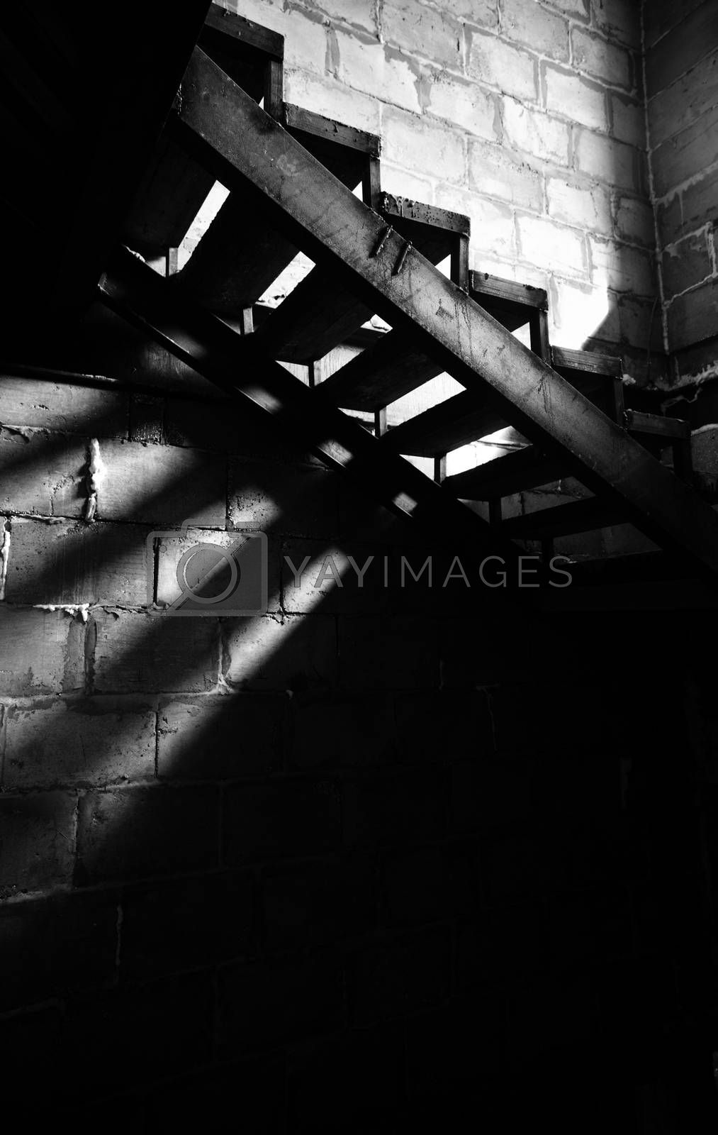 Metal old staircase in the abandoned building. Natural light and shadows