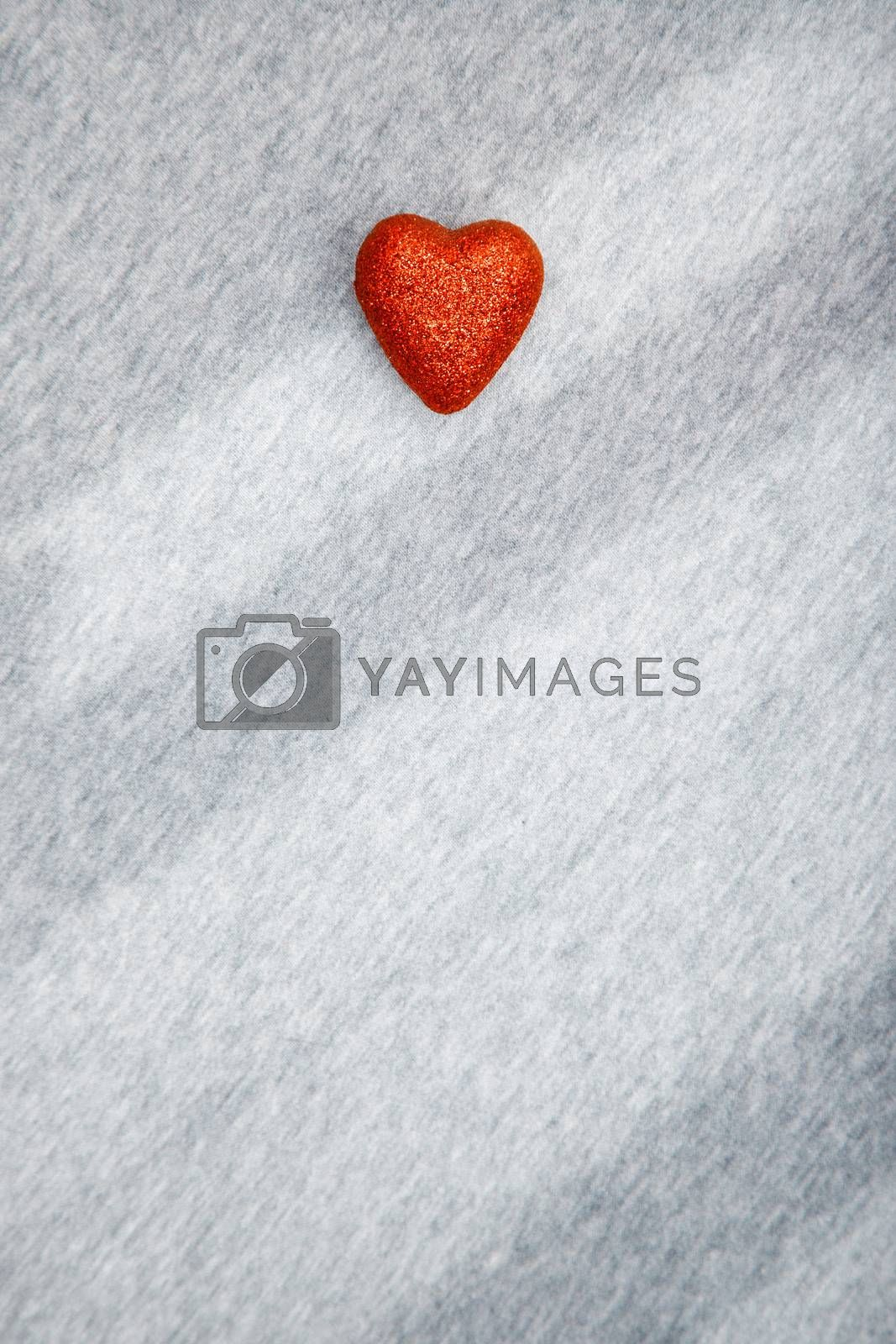 Red heart of love on a textured background with shadows