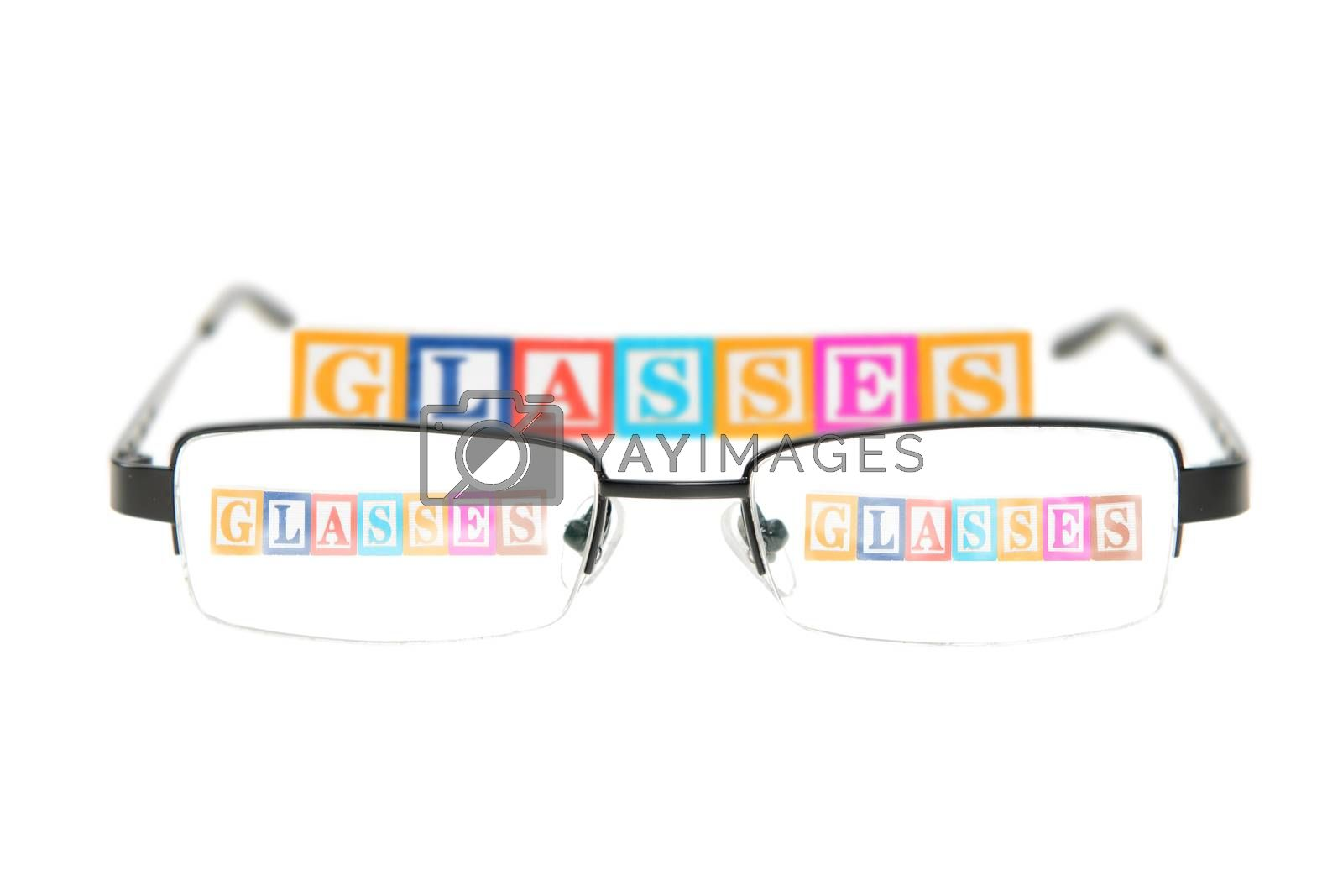 Letter blocks spelling glasses with a pair of glasses. Isolated on a white background.