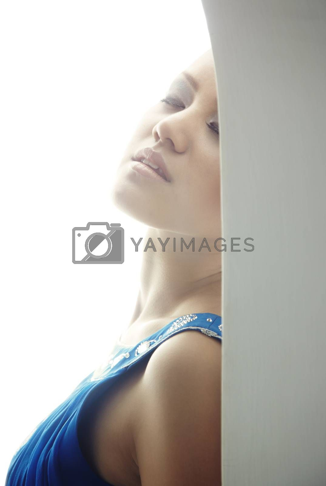 Elegant lady indoors feeling passion. Backlight from background