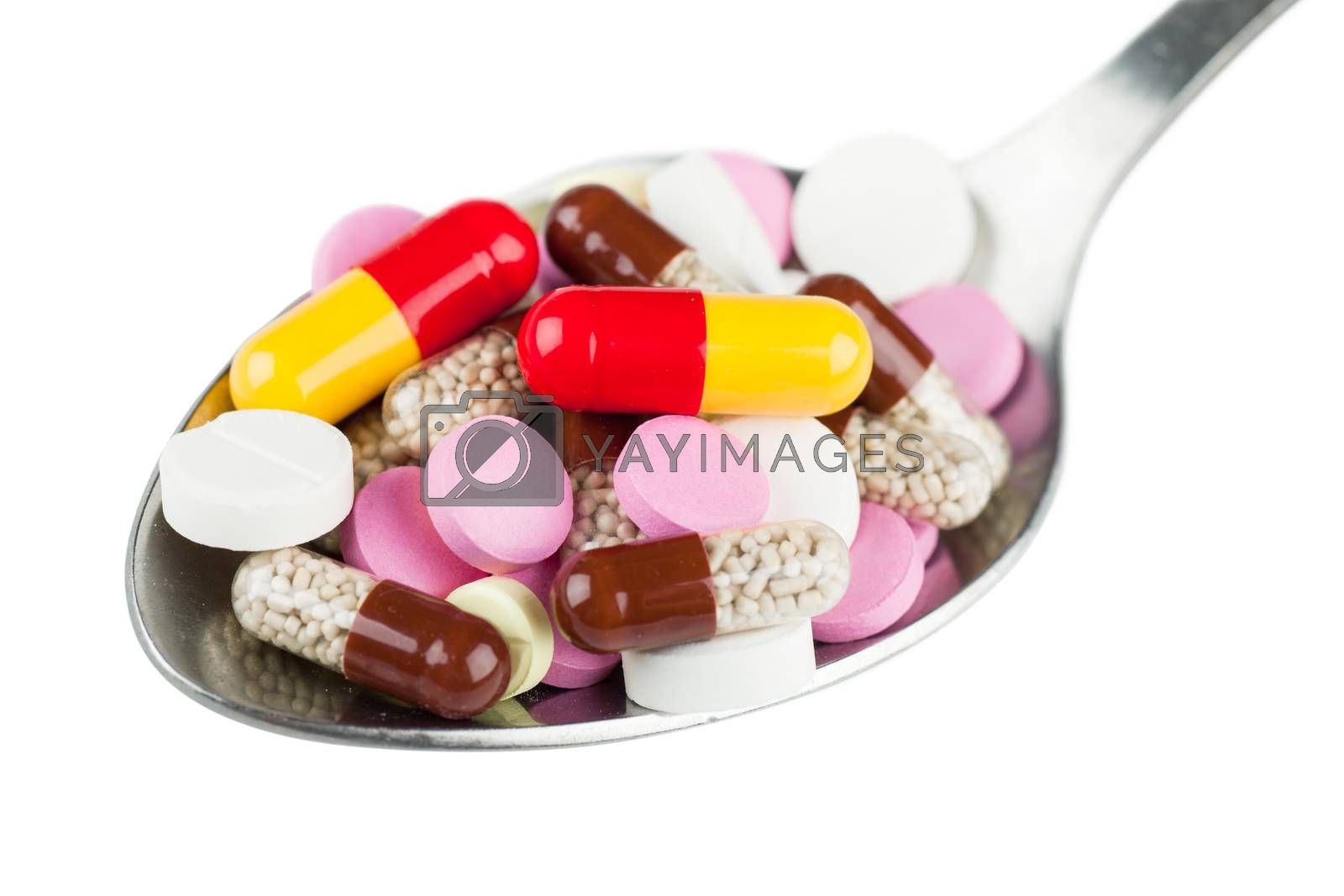 Closeup view of colorful pills in spoon isolated over white background
