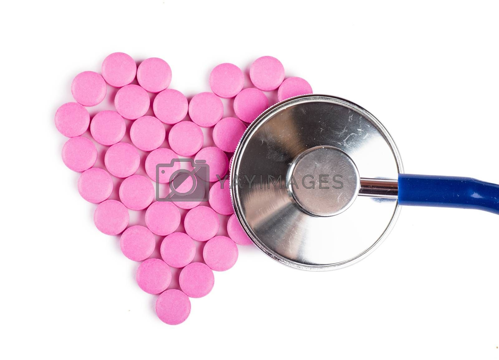 Closeup view of blue stethoscope on a heart shaped pills