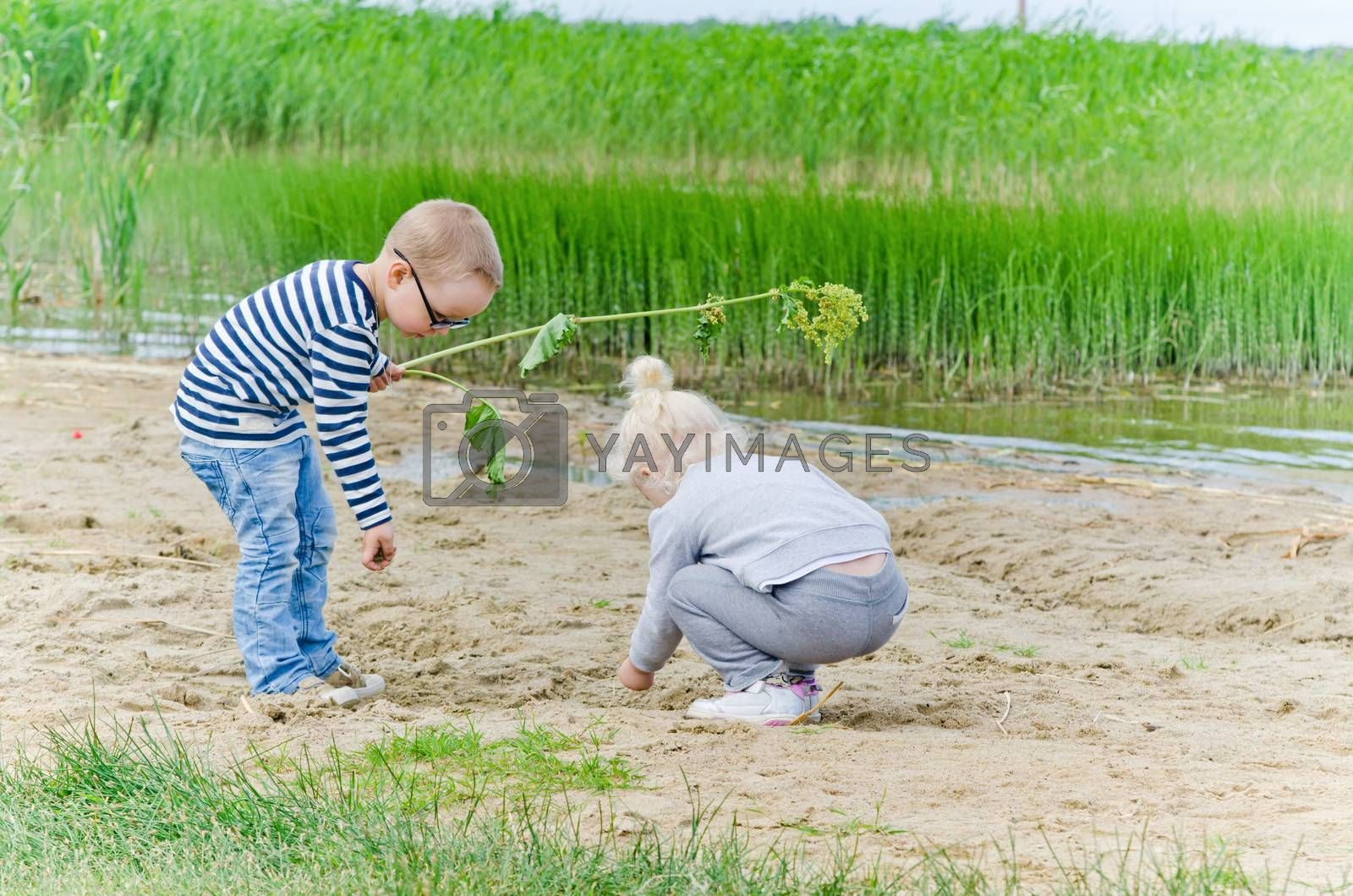 Boy and girl playing in the sand on the shore of Lake