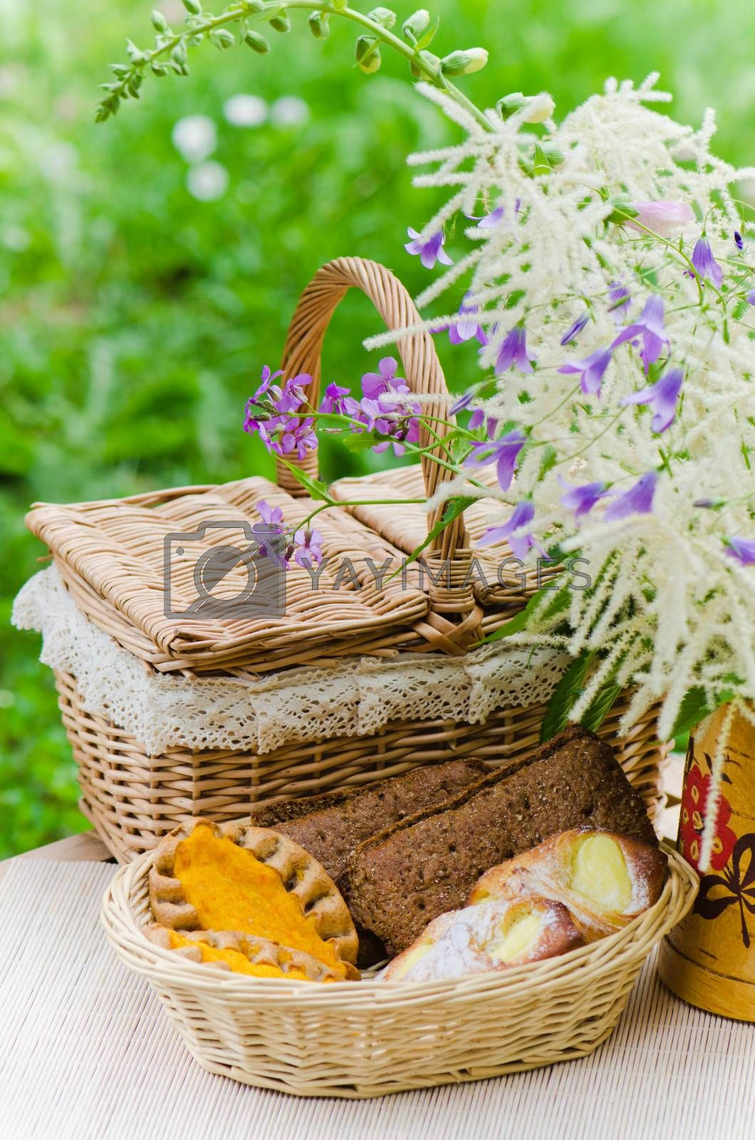 Buns in a wicker basket and a bouquet of field flowers