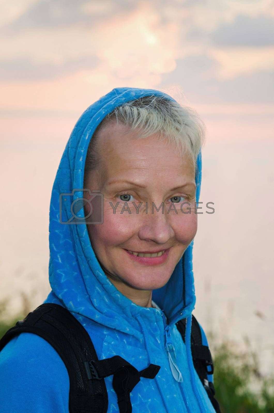 Portrait of the travelling woman of average years on a background of the evening sky