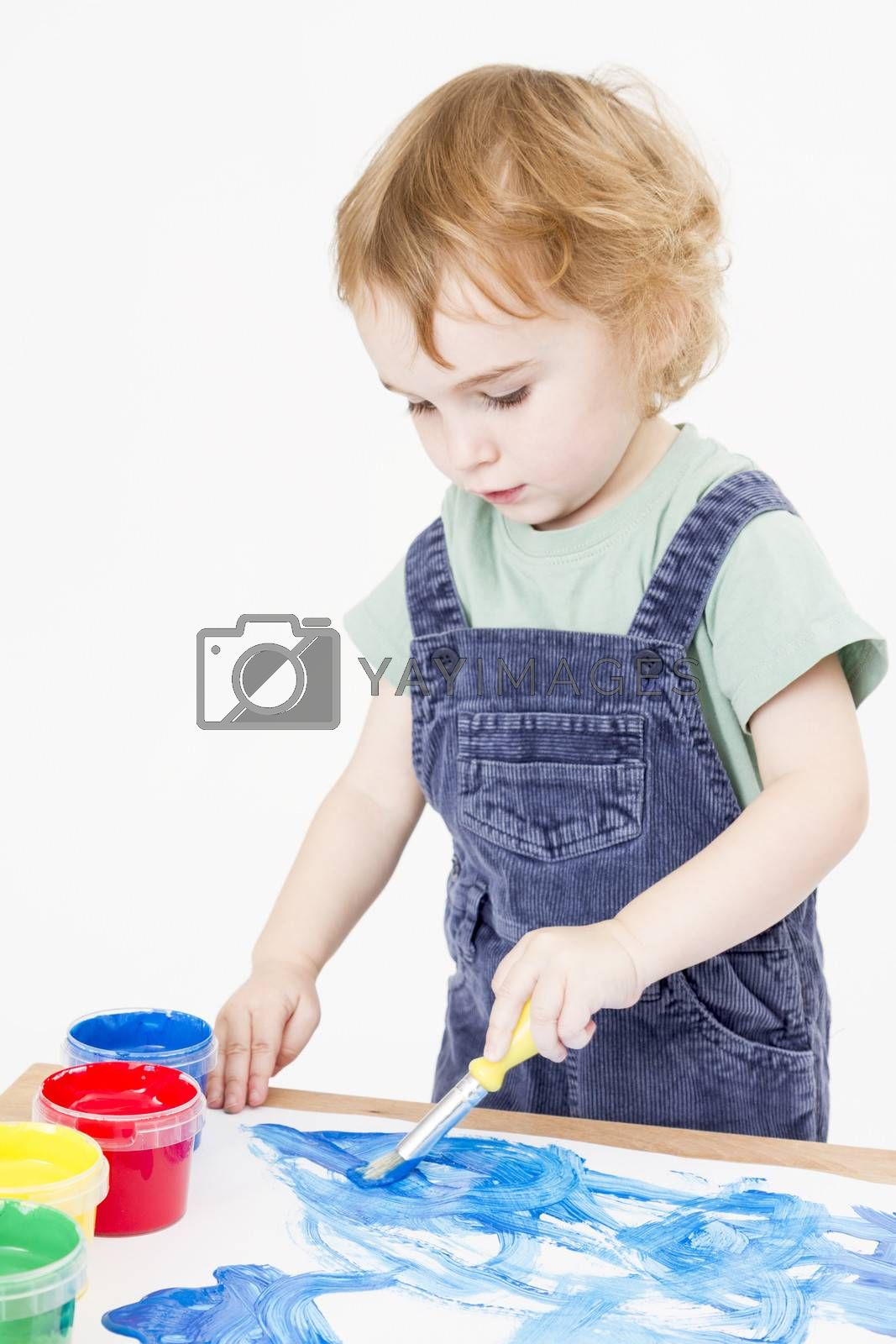 cute child making picture with brush and paint in light background