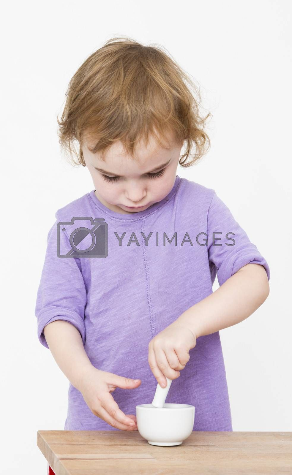 child working with mortar. neutral grey background