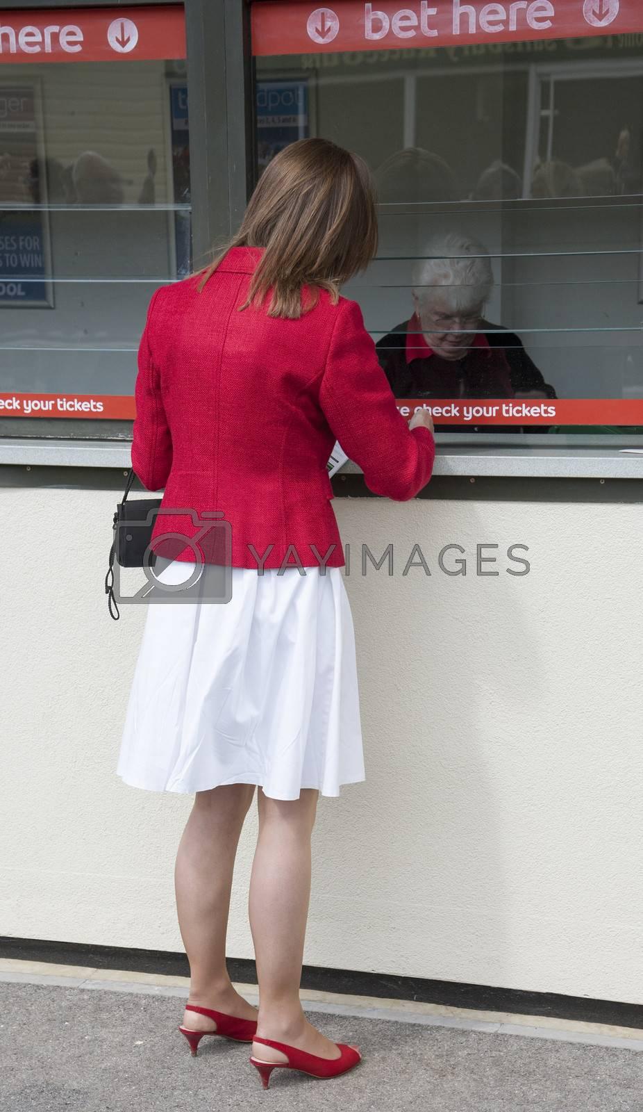 Female racegoer placing a bet