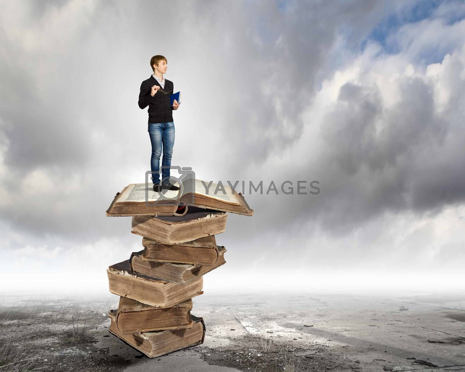 Image of little cute boy standing on pile of books