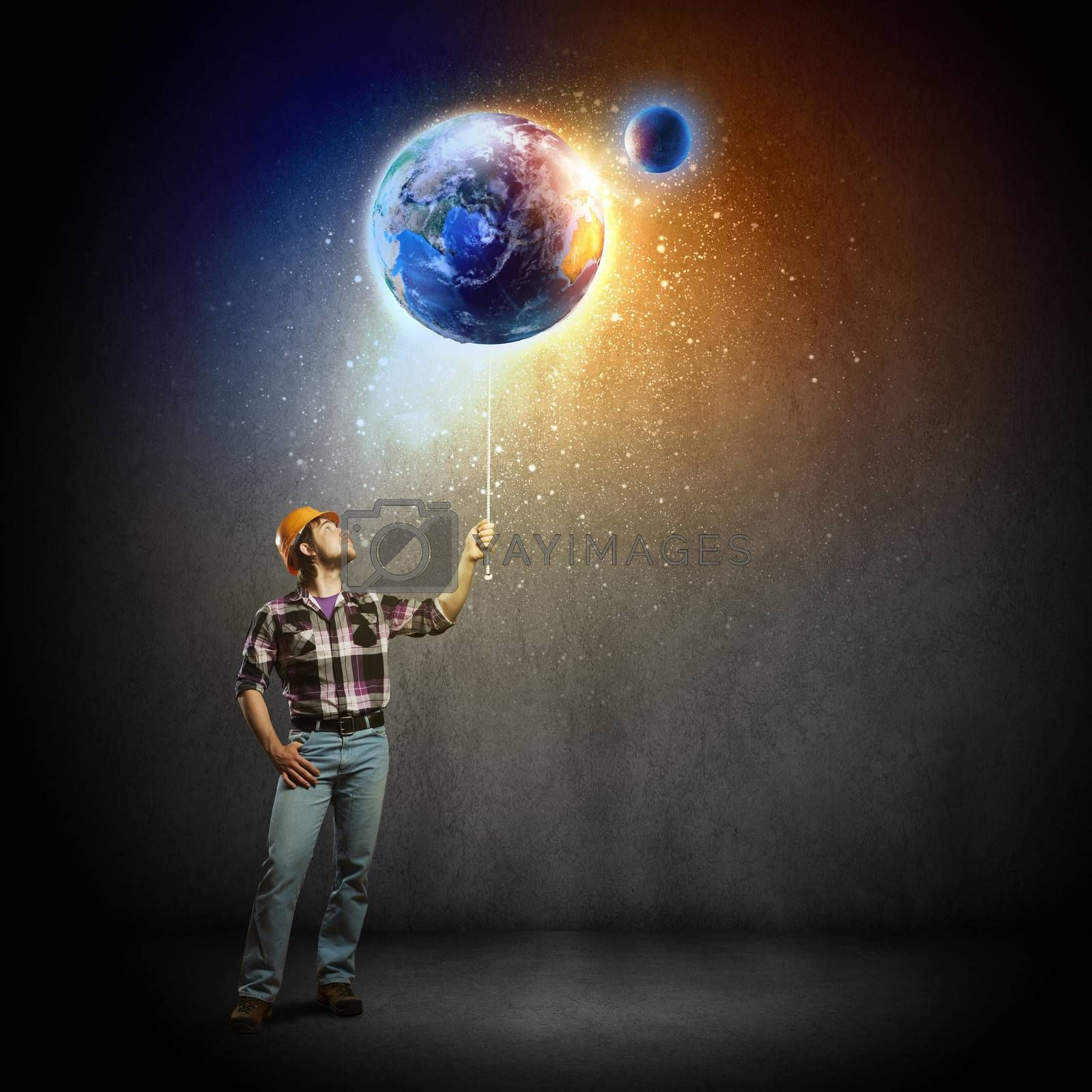 Image of man builder looking at planet Earth. Elements of this image are furnished by NASA