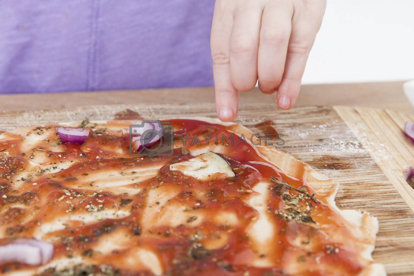 hand of young child making pizzaon wooden board