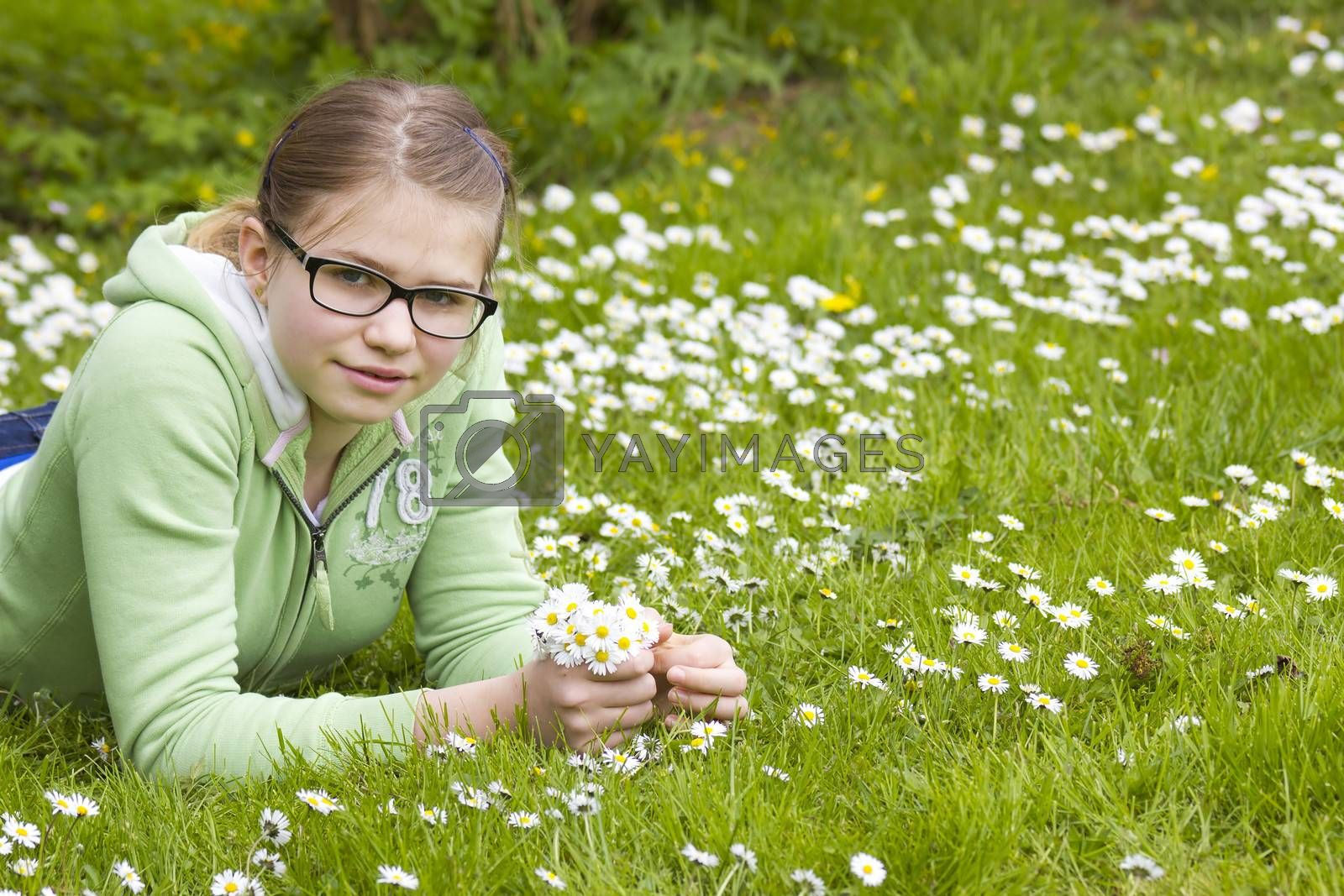 young girl picking daisies