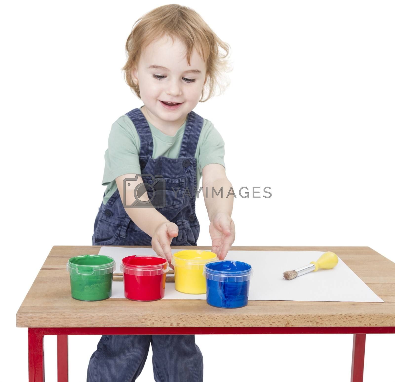 child with finger paint on wooden desk isolated in white background