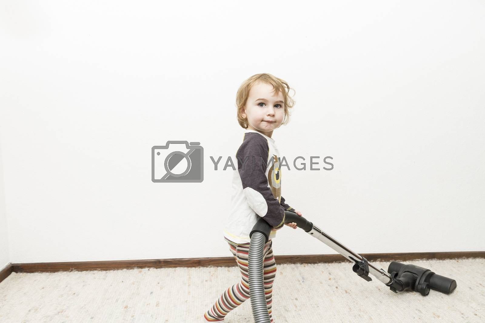 cute child doing household chore with vacuum cleaner