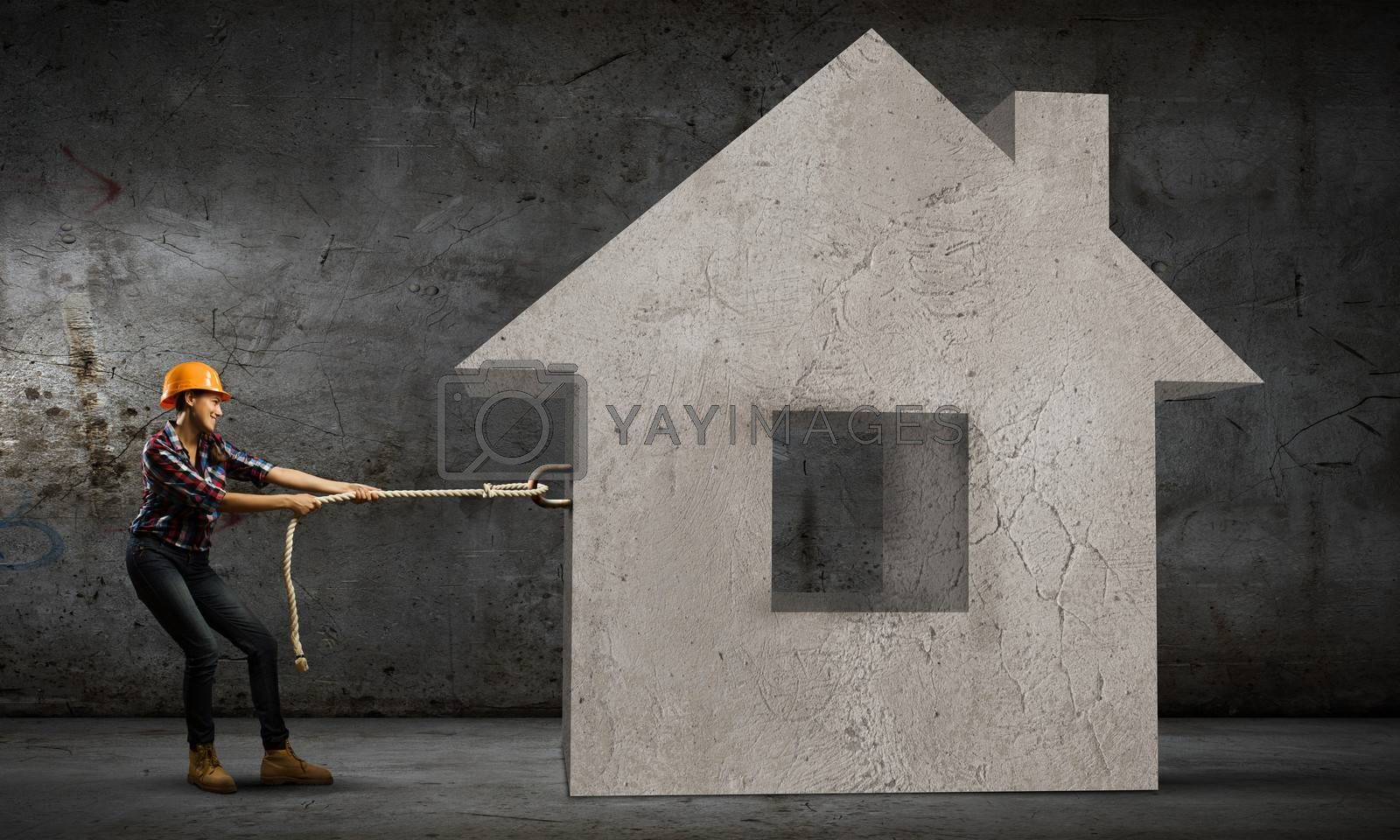 Image of woman in hardhat pulling model of house