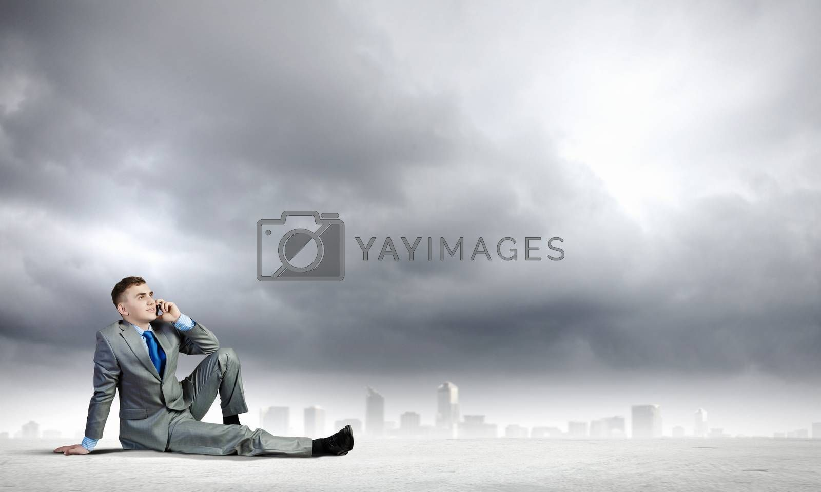 Image of young businessman with mobile phone sitting on floor