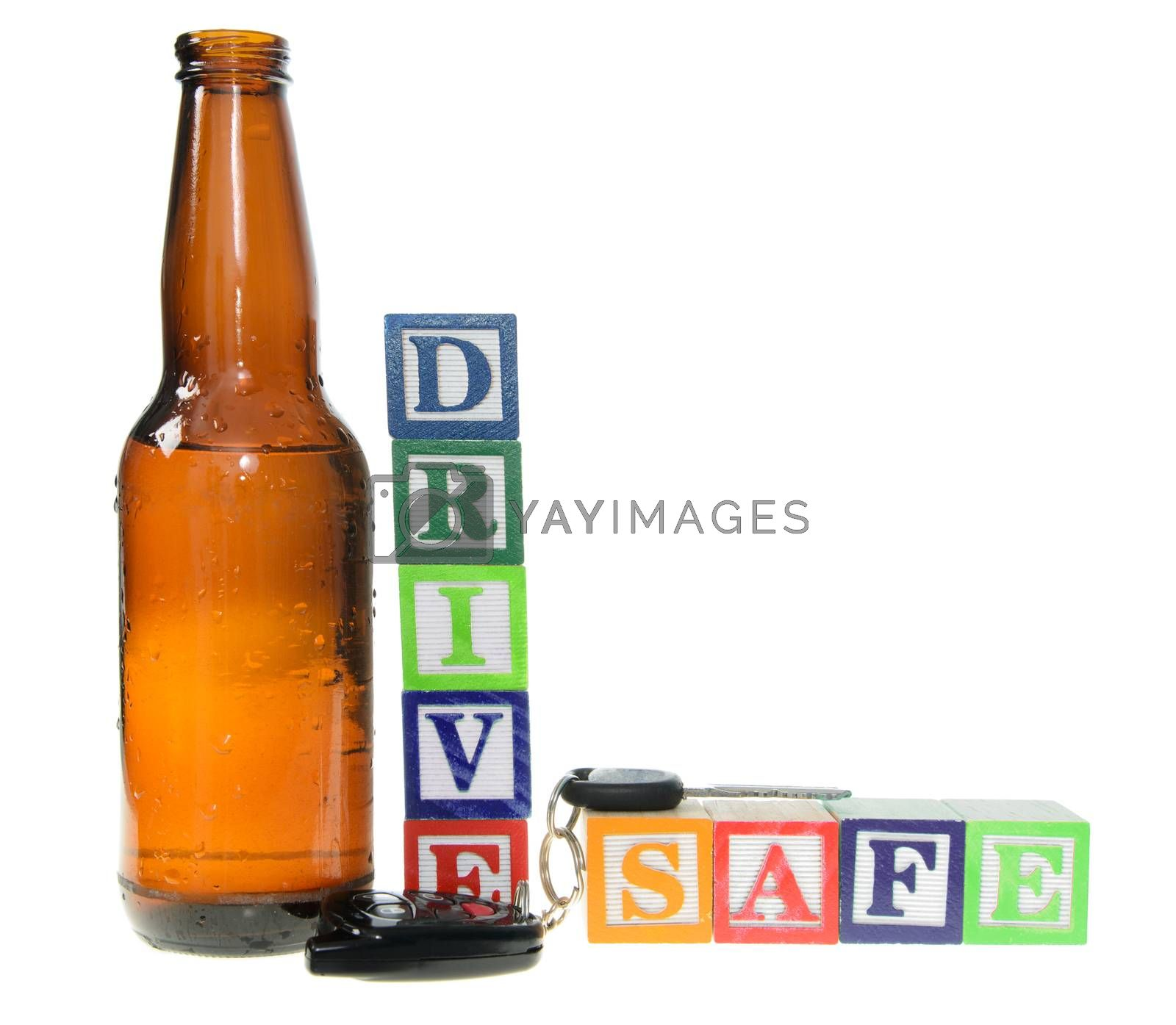 Letter blocks spelling drive safe with a beer bottle and keys. Isolated on a white background
