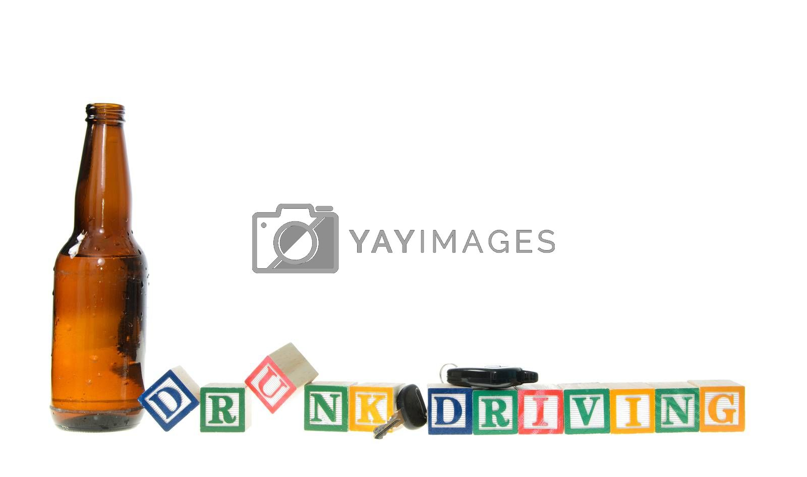 Letter blocks spelling drunk driving with keys and a beer bottle. Isolated on a white background.