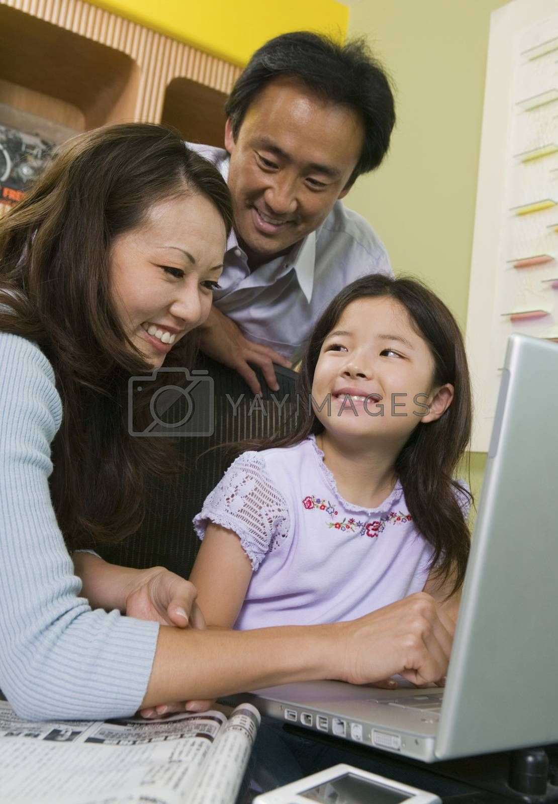 Mother and father teaching daughter to use laptop