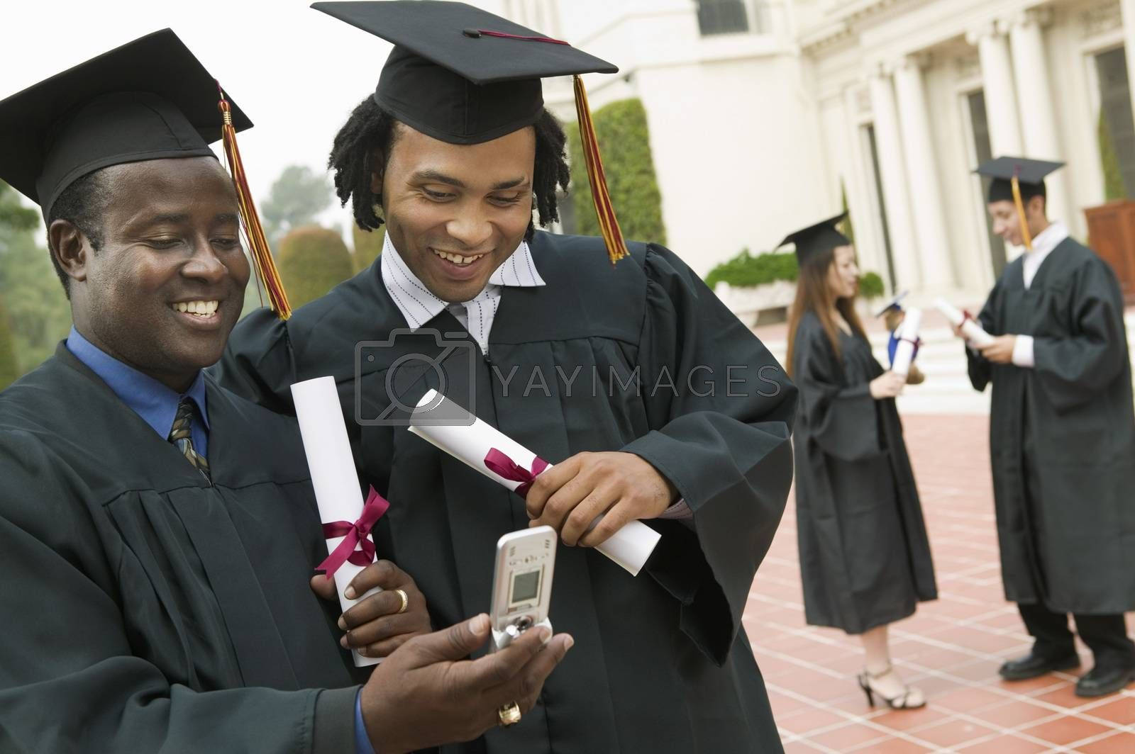 Two graduates Using Cell Phone outside