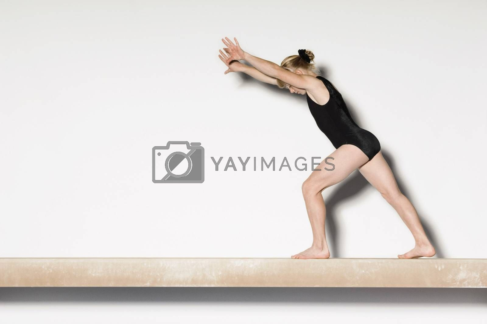 Royalty free image of Gymnast(13-15)  on balance beam preparing to do handstand side view by moodboard
