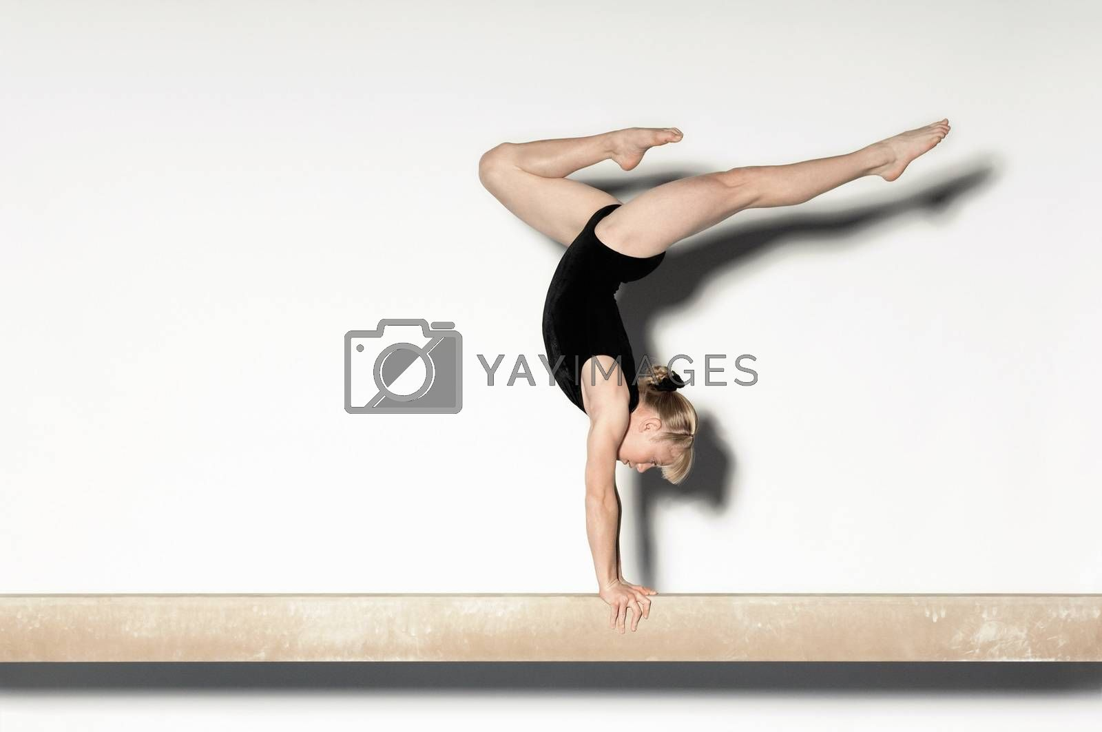 Royalty free image of Gymnast (13-15) doing handstand on balance beam side view by moodboard