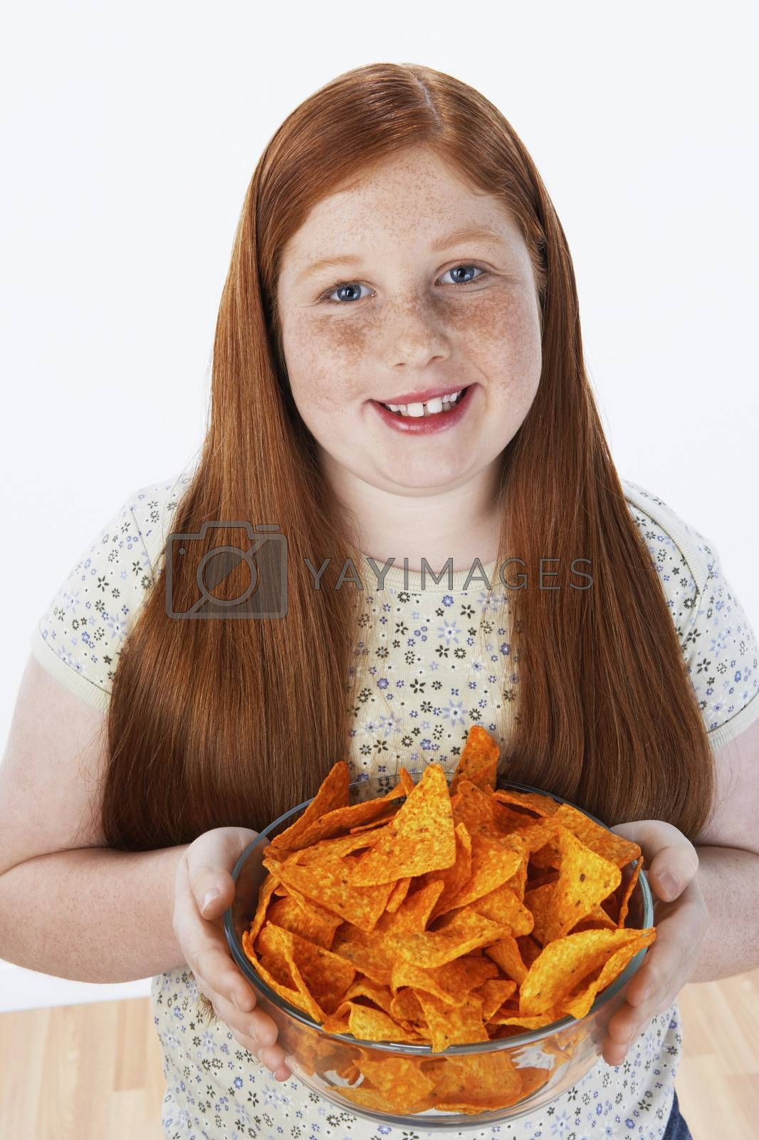 Royalty free image of Overweight girl (13-15) holding bowl of snacks portrait by moodboard