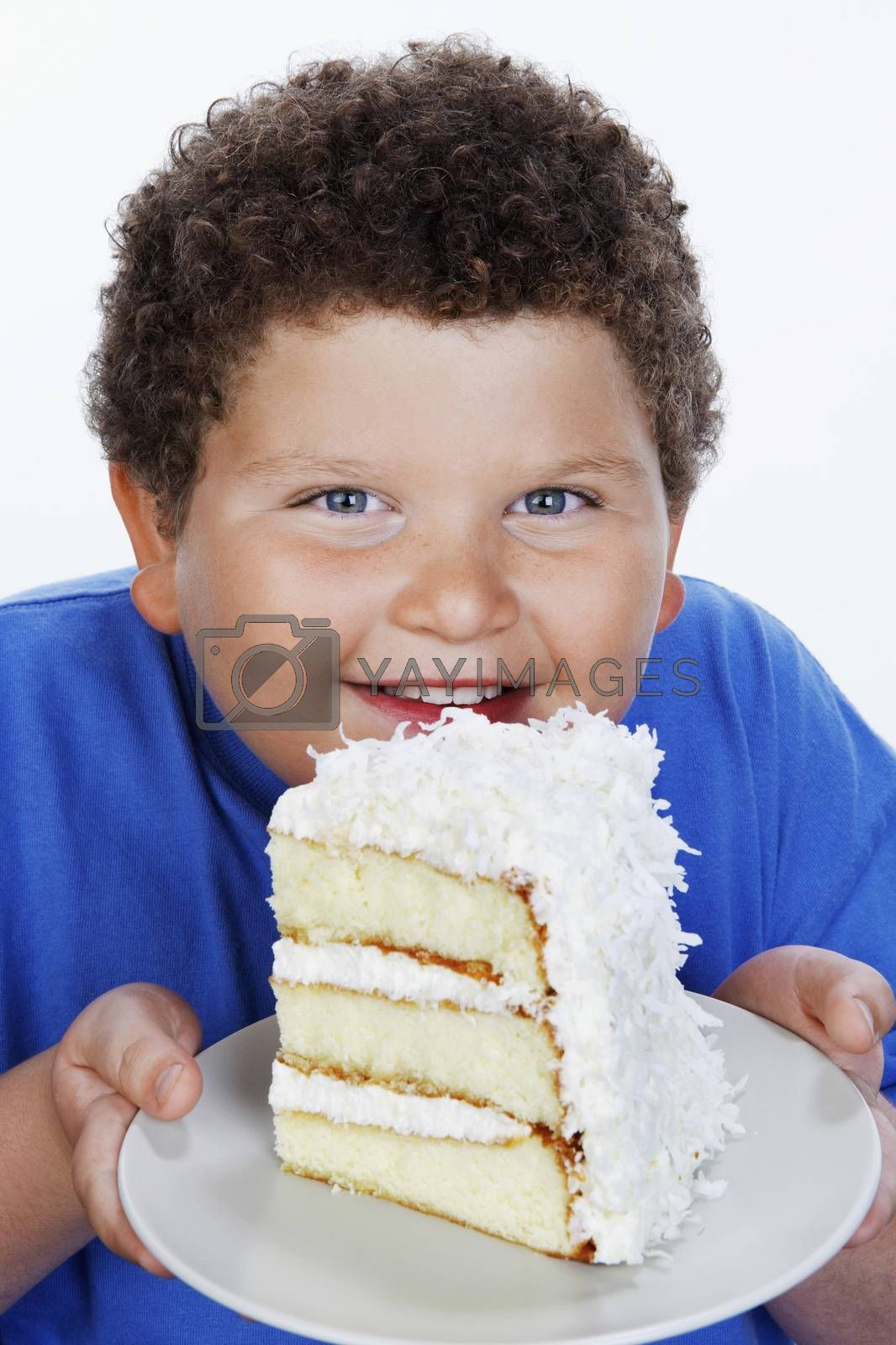 Royalty free image of Overweight boy (13-15) holding Large Slice of Cake smiling portrait by moodboard