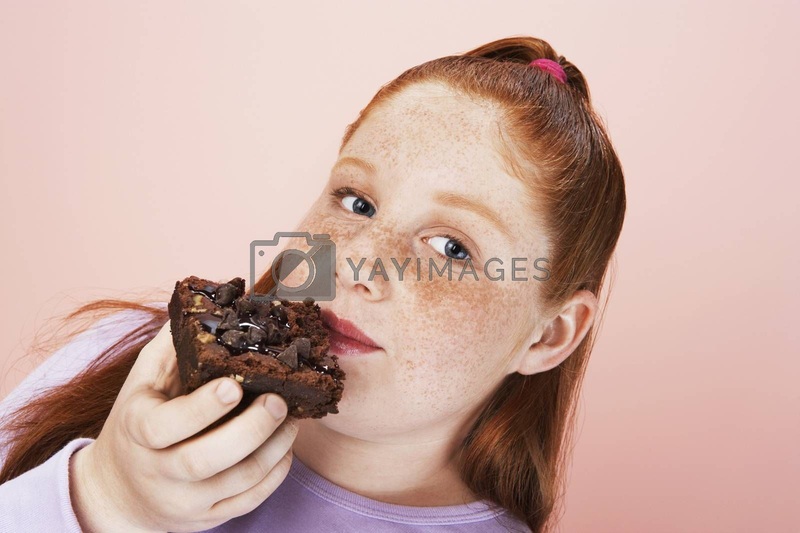 Royalty free image of Overweight girl (13-15) Eating brownie portrait close-up by moodboard