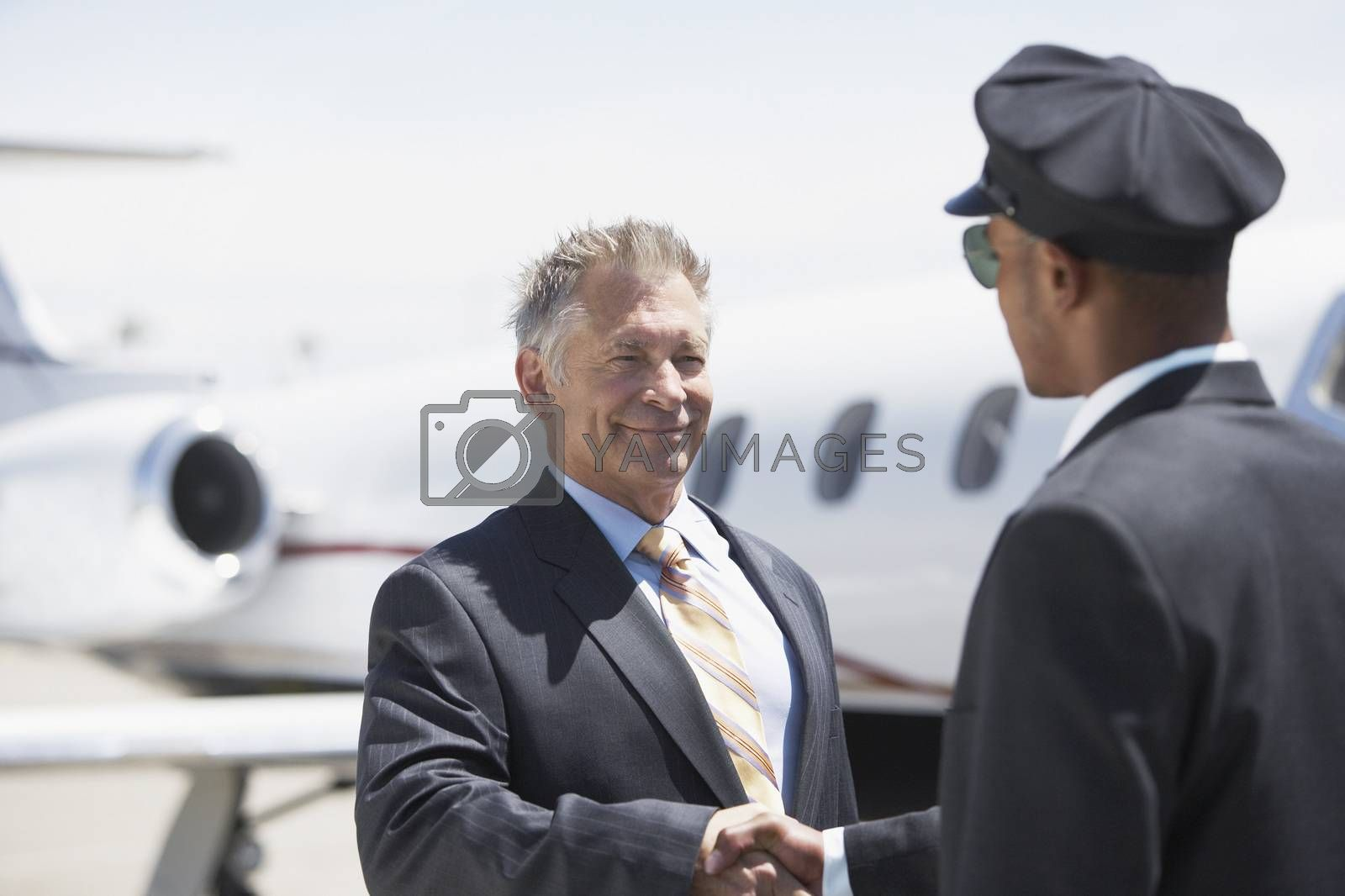 Businessman Shaking Hands With Pilot And Aircraft In Background