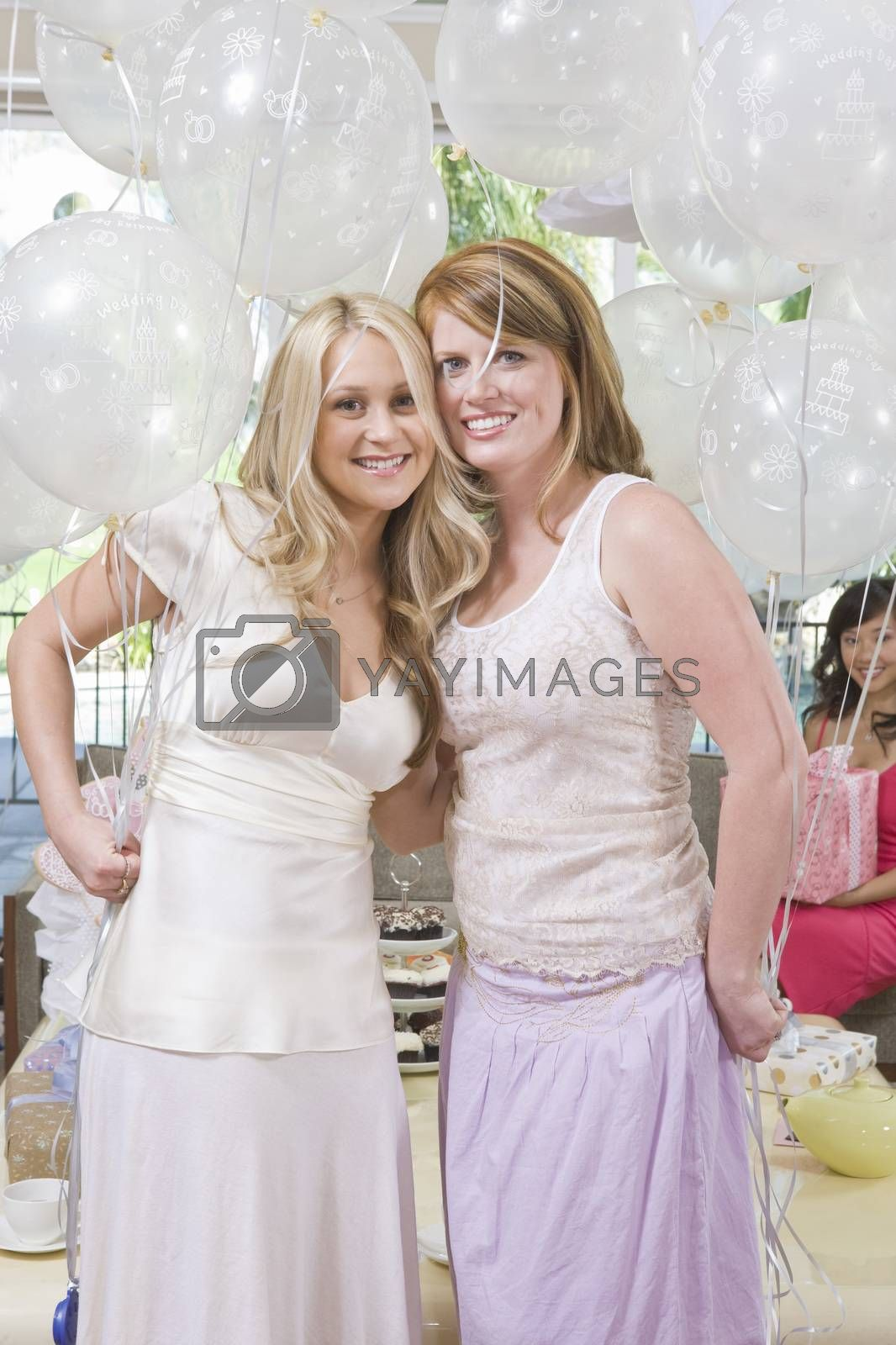 Bride And Her Friend Holding Balloons At Hen Party
