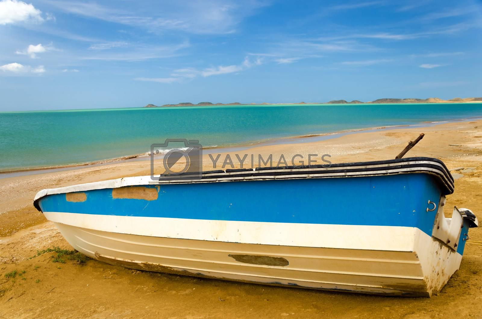Blue and white boat on a Caribbean beach in La Guajira, Colombia