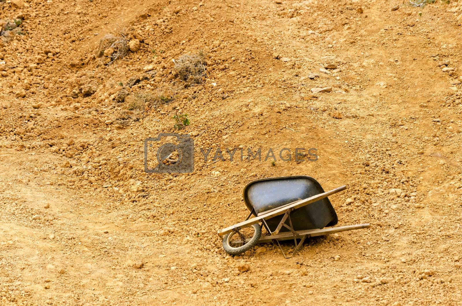 Black wheelbarrow in a dry barren setting
