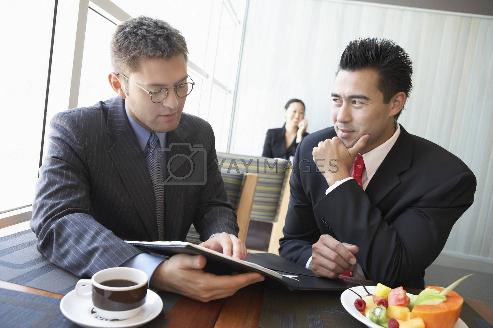 Businessmen Discussing Contract In Restaurant