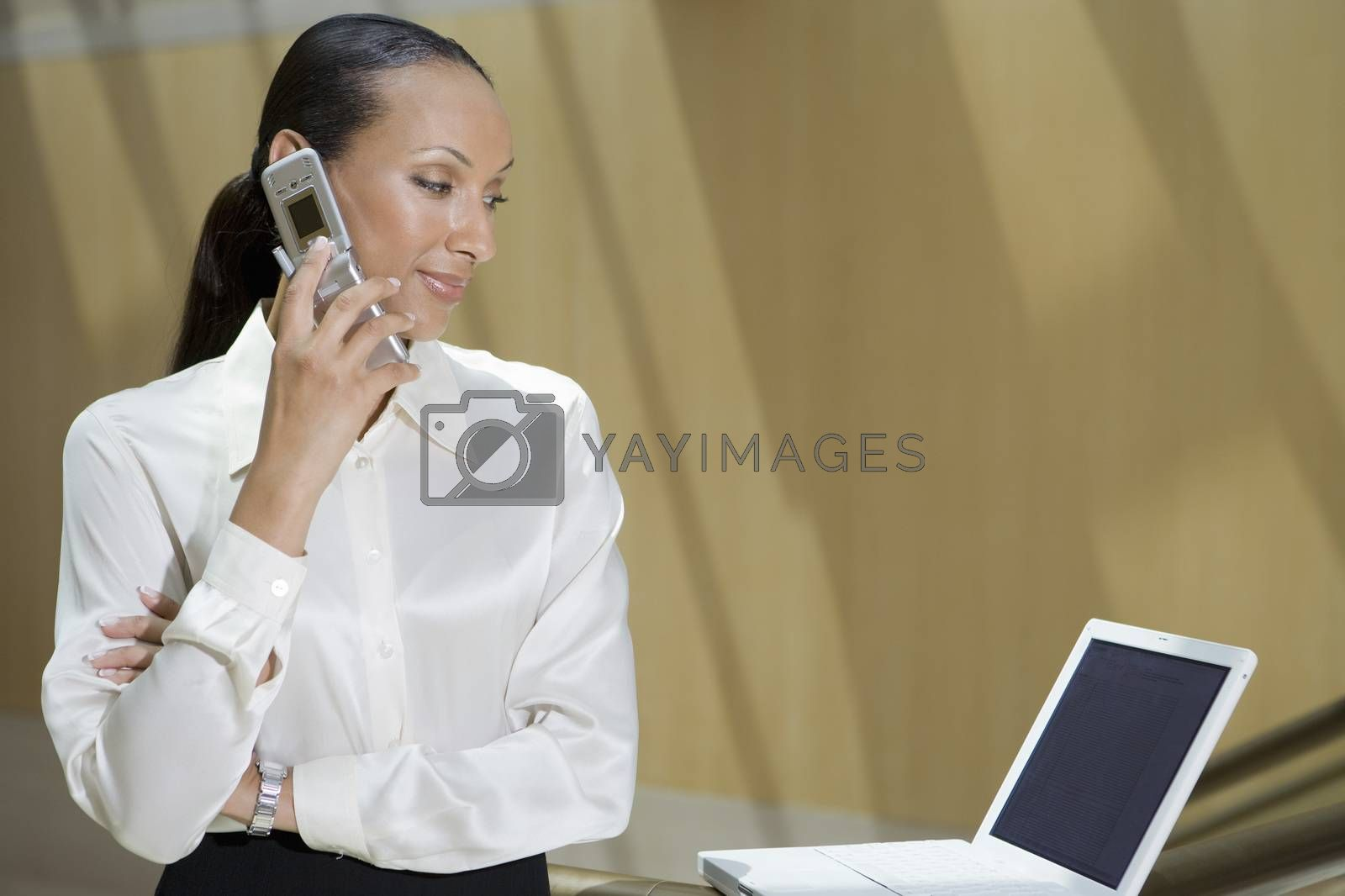 Businesswoman Using Mobile Phone While Looking At Laptop