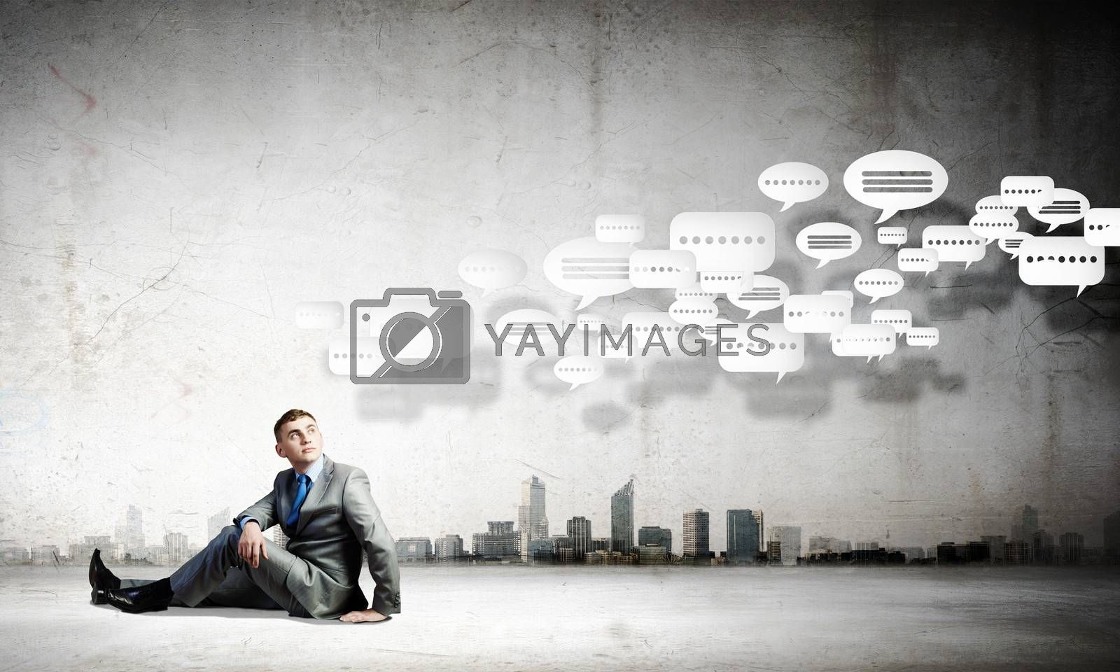 Image of young businessman sitting on floor
