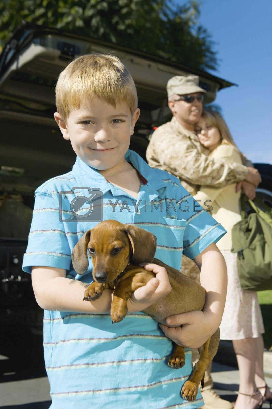 Boy Carrying Dog With Parents In Background