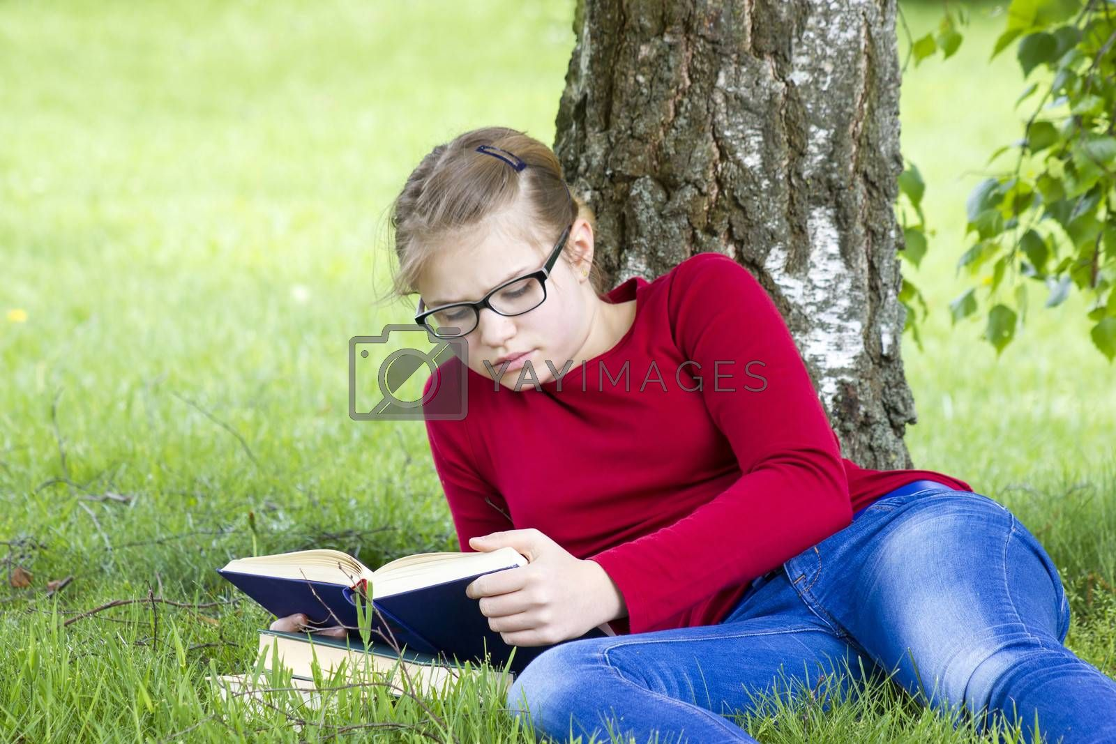 Young girl reading book in park in spring day